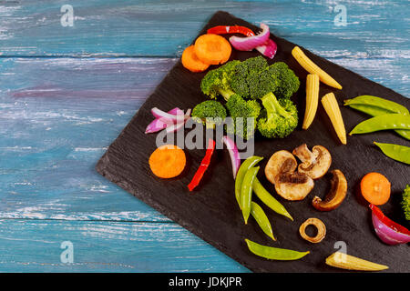 Variety of raw green vegetables salads, lettuce, bok choy, corn, broccoli, savoy cabbage, colorful young carrots - Stock Photo