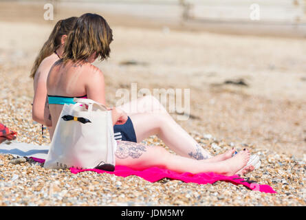 Pair of girls or young women sitting on a beach sunbathing in bikinis on a hot day in Summer in the UK. - Stock Photo