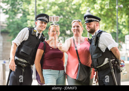 London, UK. 21st June, 2017. UK Weather: Canadian tourist sisters pose with metropolitan police officers for a selfie - Stock Photo