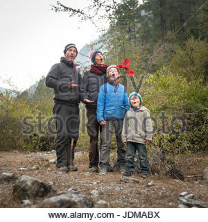 A European family sings Christmas carols while camping in India. - Stock Photo