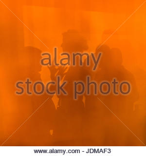 A woman and man play hand shadow puppet on a colorful orange wall. - Stock Photo