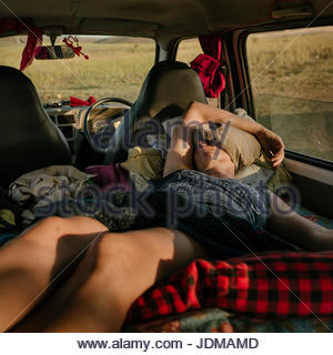 A German woman naps inside a camper van in India. - Stock Photo