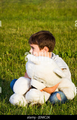 Lonely boy hugging teddy bear and sitting on the grass - Stock Photo
