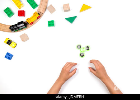 Kids hands playing with fidget spinner toy. Many colorful toys on white background. Top view - Stock Photo