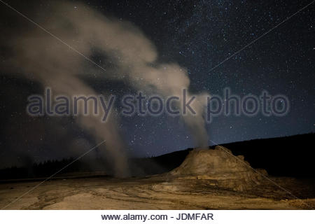 Milky Way above Castle Geyser emitting steam. - Stock Photo