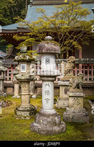 Stone lanterns and Japanese architecture in Nara Park, Nara, Nara Prefecture, Honshu Island, Japan. - Stock Photo