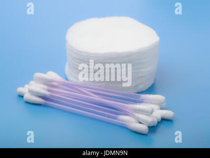 Cotton pads and buds on blue background - Stock Photo
