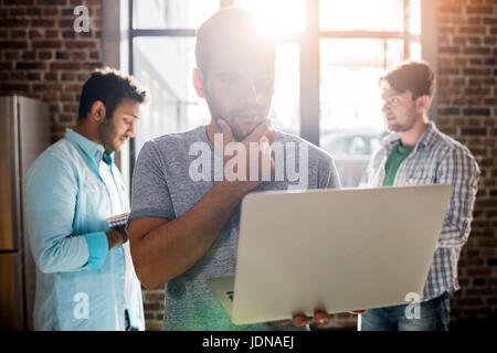 young professionals working on new business project with laptop in small business office - Stock Photo
