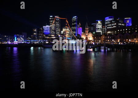 Beautiful scene of colorful Sydney city skyline by night at Campbell's Cove during Vivid Sydney Lights Festival. - Stock Photo