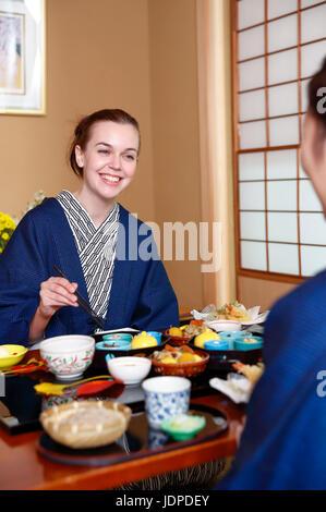 Caucasian woman wearing yukata eating at traditional ryokan, Tokyo, Japan - Stock Photo