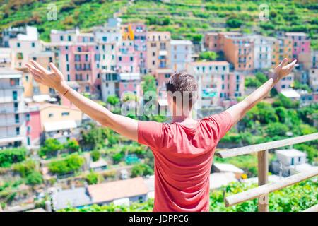 Tourist looking at scenic view of Manarola, Cinque Terre, Liguria, Italy - Stock Photo