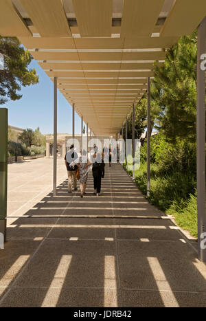 Rear view of museum visitors walking down a route of passage at the Israel Museum, Jerusalem, famous for its art - Stock Photo