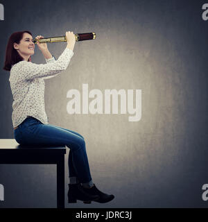 Portrait of positive, young businesswoman looking through a spyglass, student smiling ready for adventure. Business - Stock Photo