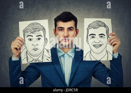 Depressed Businessman holding two white papers with different emotions drawn. Change your mask between confused - Stock Photo