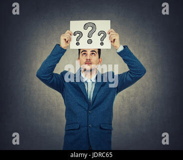 Portrait of confused, thinking young businessman seeks a solution looking up, holding a paper over head with drawn - Stock Photo