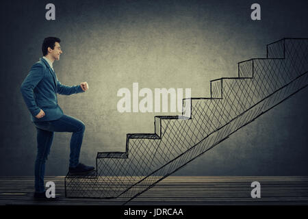 Confident, smiling businessman climbing imaginative drawn stairs. Ambitions concept, pathway of opportunity and - Stock Photo