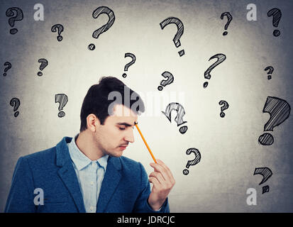 Thoughtful businessman holding a pencil pointed to face, drawing different interrogation marks like questions escaping - Stock Photo