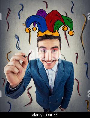 Closeup of a smiling businessman as clown drowning himself a jester, harlequin hat. Human expression and emotions, - Stock Photo