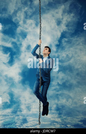 Afraid Businessman climbing on a chain rope try to reach the sky. Business success, opportunity and risk concept. - Stock Photo