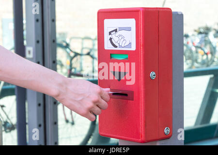 Validate a ticket at a red ticket validation machine for the underground from the side - Stock Photo