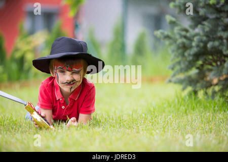 Cute school boy, playing games, painted as pirate, holding sword, play in garden, outdoor summertime - Stock Photo