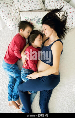 Beautiful pregnant young mother and her two children, boys, lying in bed at home - Stock Photo