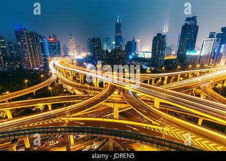 View over the famous highway intersection in Shanghai, China, with modern architecture. Shanghai skyline by night. - Stock Photo