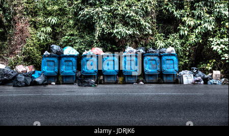 A Row of Garbage Cans Lined Overflowing at the Side of the Road - Stock Photo