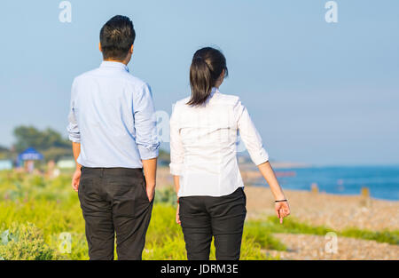 Young Asian couple dressed smartly walking on a beach on a warm summer evening in the UK. - Stock Photo