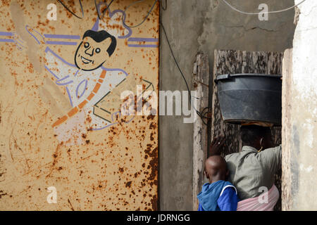 Drawing of a cook on the rusty wall. Senegalese woman is carrying a plastic bucket on the head and has a child fastened - Stock Photo