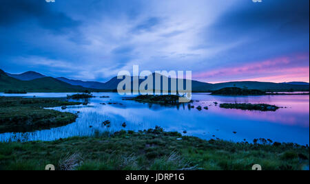 Reflections of the late evening sky on midsummer in the small lochan on Rannoch Moor, near Glencoe in Scottish Highlands - Stock Photo