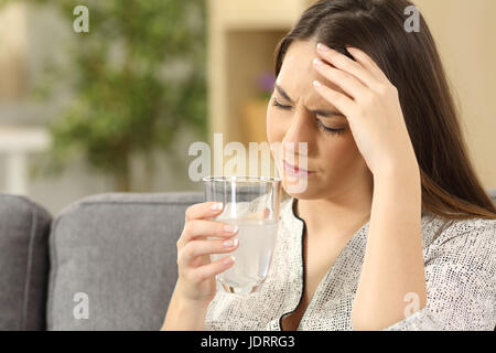Woman suffering head ache holding a water glass sitting on a couch in the living room at home - Stock Photo