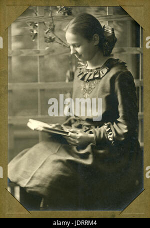 Antique c1910 photograph, portrait of a girl reading a book. Location is probably in or near  Mankato, Minnesota. - Stock Photo