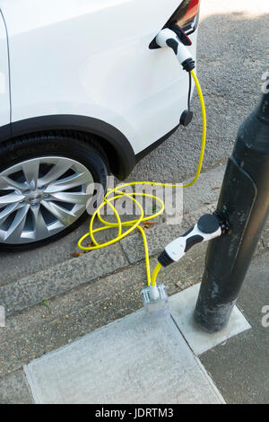 An electric car charger conversion by Ubitricity: smart cable on a street lamp which can now be used to charge a - Stock Photo