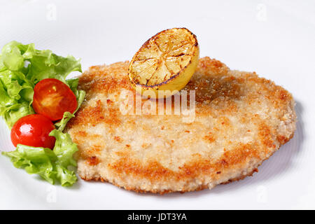 German schnitzel with lemons and limes, tomatoes and lamb's lettuce salad - Stock Photo