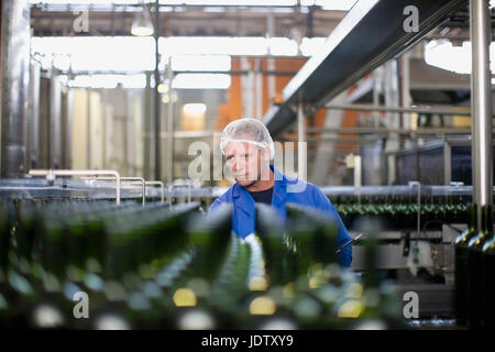 Worker examining bottles in factory - Stock Photo