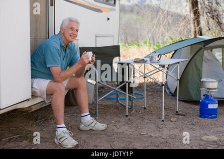 Older man camping with RV - Stock Photo