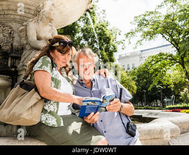 Older couple reading travel guide - Stock Photo