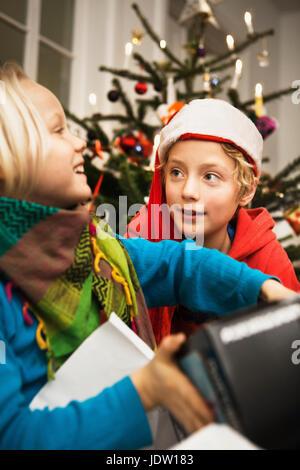 Children opening Christmas gifts - Stock Photo