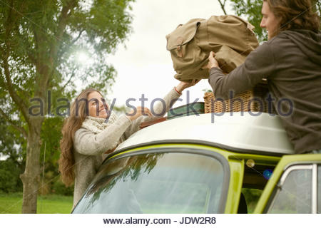 Couple loading luggage onto van - Stock Photo