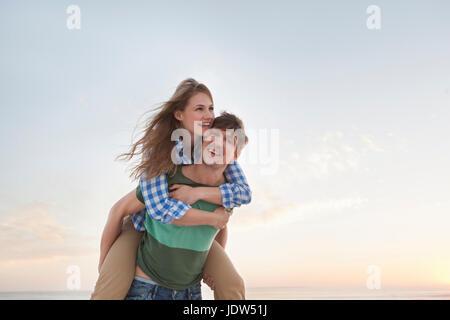 Couple on beach, man giving woman piggy back - Stock Photo