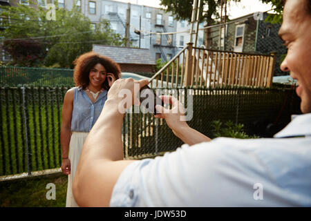 Young man photographing woman in garden - Stock Photo