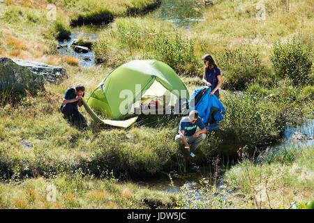 Three people camping by stream, Chamonix, Haute Savoie, France - Stock Photo