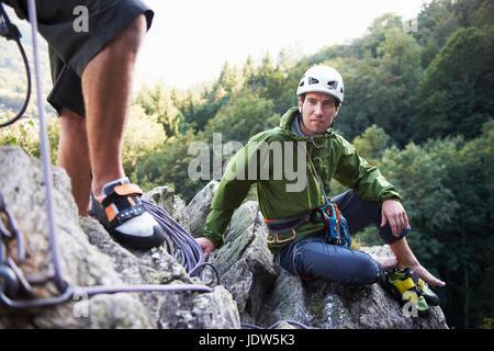 Rock climber sitting on rocks, Chamonix, Haute Savoie, France