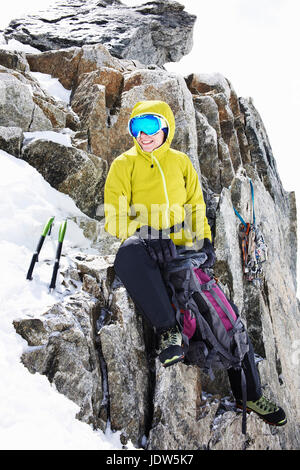Woman in climbing gear resting on mountain - Stock Photo