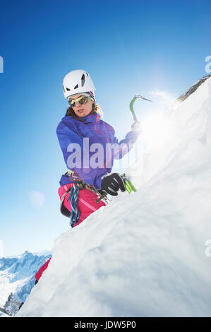 Female mountain climber using ice pick - Stock Photo