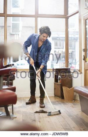 Man sweeping barbershop floor with broom - Stock Photo