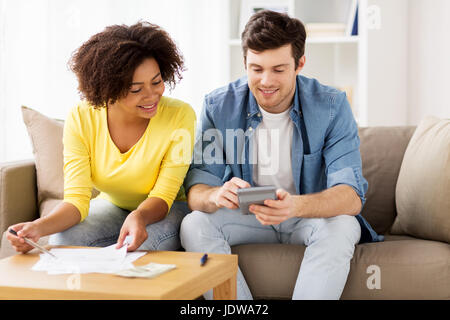 happy couple with papers and calculator at home - Stock Photo
