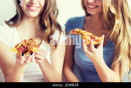 happy friends or teen girls eating pizza at home - Stock Photo