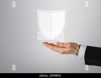close up of man with virtual antivirus shield icon - Stock Photo
